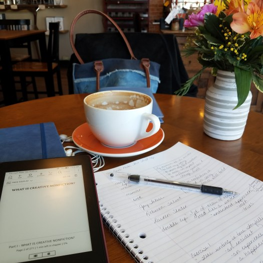 Ink pen on a notebook, Kindle and another notebook, earbuds, a cup of coffee and a vase of flowers on a coffee shop table.  A writing station.