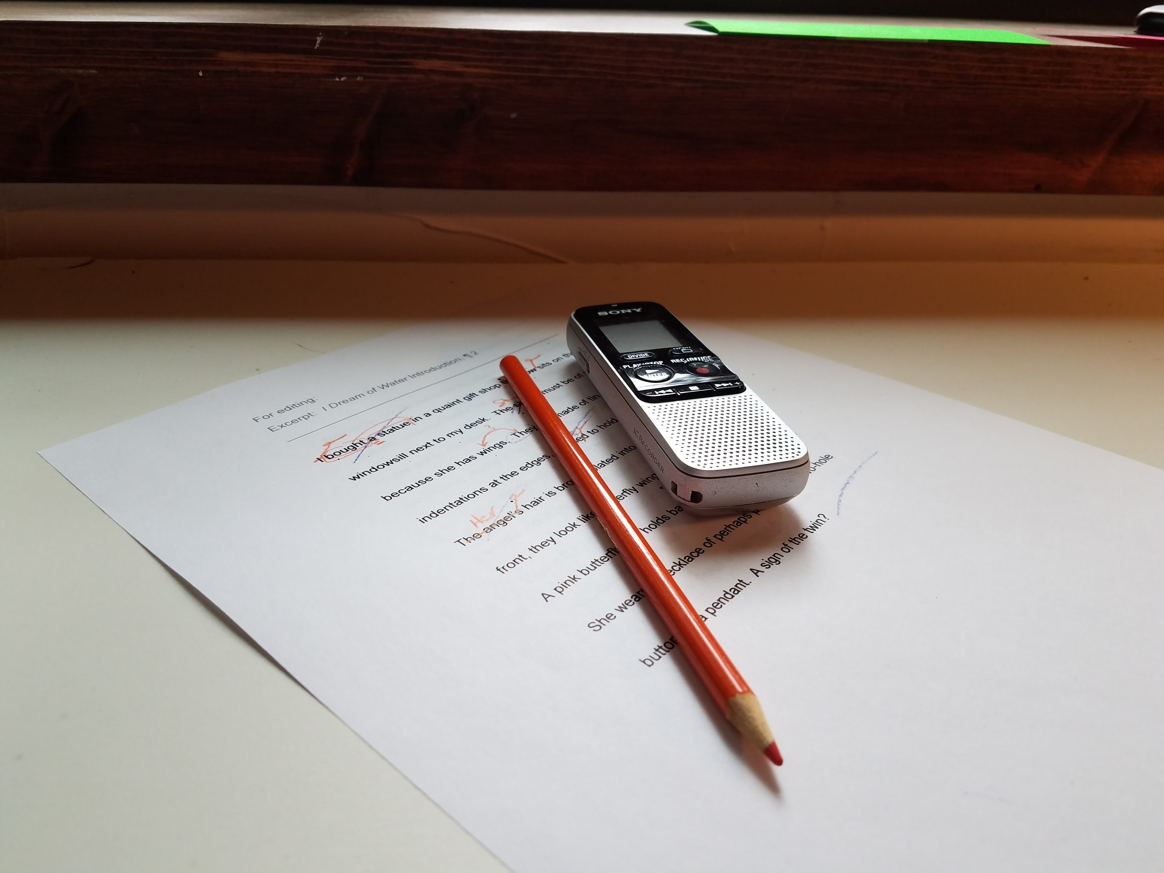 Orange colored pencil and voice recorder laying on top of printed page for editing