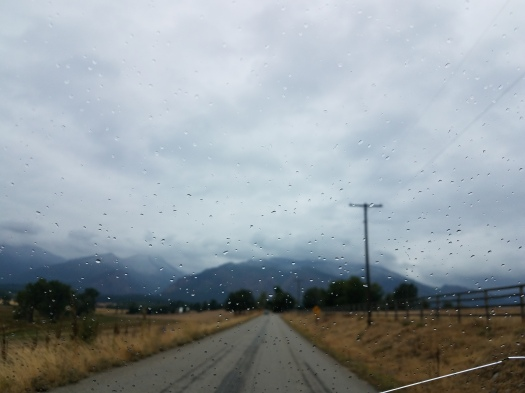 A road to the cloud shrouded mountains through a cracked and rain-speckled windshield.  (Photo:  Theresa Duncan)
