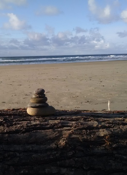 Stacked stones on a log on an Oregon beach.  Photo:  Theresa Duncan